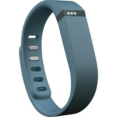 Podomètre et tracker FitBit Bleu Ardoise. Durant la journée, il mesure le nombre de pas effectués, la distance parcourue et les calories brûlées. La nuit, il analyse le cycle de sommeil et réveille en silence au matin.