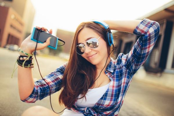 dancing-hipster-girl-with-headphones-in-city-during-summer-picture-id451568915